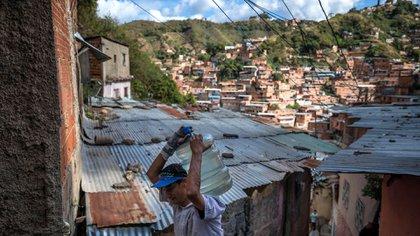 """ACOMPAÑA CRÓNICA VENEZUELA AGUA***AME7356. CARACAS (VENEZUELA), 23/02/2021.-Fotografía del 11 de febrero del 2021 donde se observa a un hombre cargar una botella de 25 litros de agua, en Caracas (Venezuela). El experto en políticas públicas y director de la ONG local Ojo Avizor, Norberto Baussón, advierte a Efe que la falla en el suministro de agua corriente afecta, en el mejor de los casos, a casi 9 de cada 10 hogares del país. """"El porcentaje por región varía entre un 87 % y un 99 % de afectación por falta de agua. Eso lo que quiere decir es que es un problema nacional, no un problema asociado a una región o alguna circunstancia"""", señala. EFE/ Miguel Gutiérrez"""