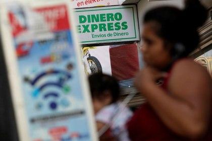 FOTO DE ARCHIVO. Una mujer habla por teléfono frente a una oficina de cambio de moneda en Ciudad Juárez, México. 1 de julio de 2017. REUTERS/José Luis González