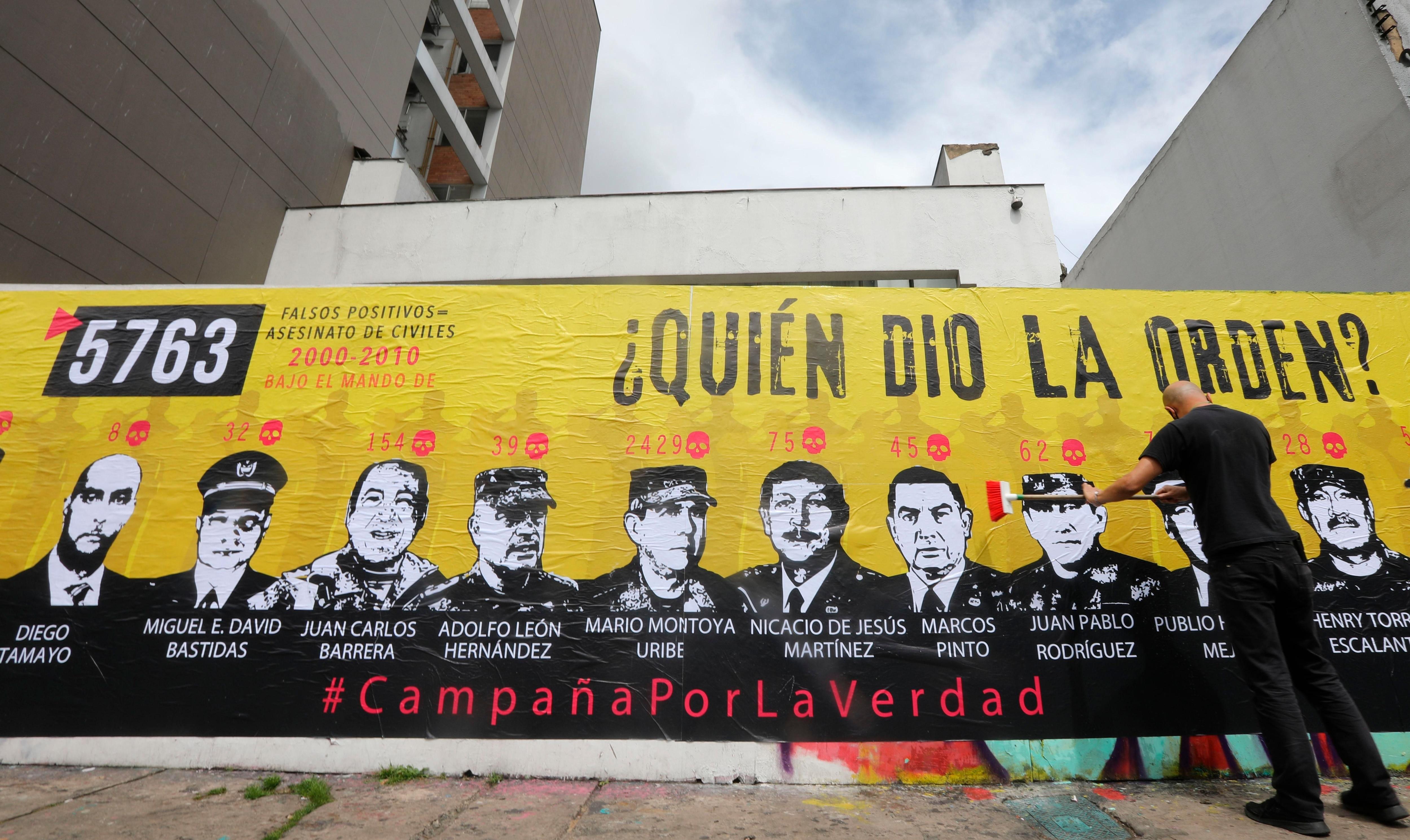 Un hombre participa hoy en la elaboración de un mural sobre los falsos positivos, en Bogotá (Colombia). EFE/ Carlos Ortega