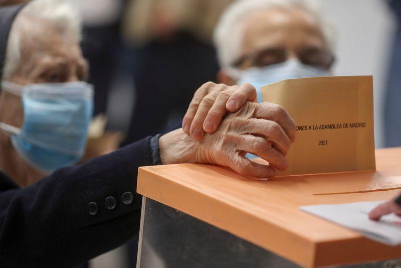 Una persona deposita su voto durante las elecciones autonómicas de Madrid, España, 4 de mayo de 2021. REUTERS/Susana Vera