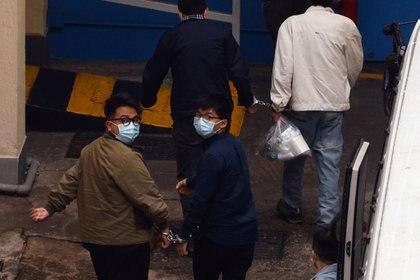 Ivan Lam y Joshua Wong al llegar al Centro de Recepción Lai Chi Kok del Departamento de Servicios Correccionales de Hong Kong (Reuters)