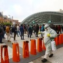 Cleaning staff using disinfectants at subway entrances as people line up to enter the Constitucion transfer center, one of the most important in the city, in response to the outbreak of coronavirus disease (COVID-19) in Buenos Aires, Argentina March 19, 2020. Picture taken March 19, 2020 REUTERS/Matias Baglietto
