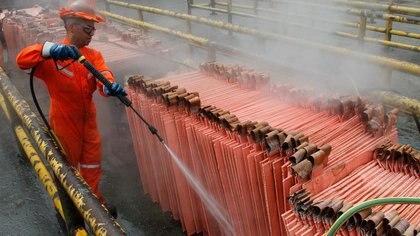 Un trabajador limpiando cátodos de cobre en la refinería de Codelco en Ventanas, Chile. La minería fue duramente afectada por la pandemia. REUTERS/Rodrigo Garrido
