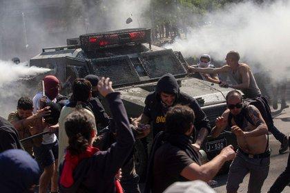 Manifestantes se enfrentan a un vehículo policial en Santiago (Foto: Claudio Reyes/ AFP)