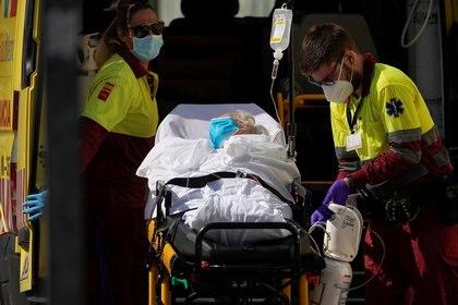 Trabajadores de la salud que usan equipo de protección son vistos con un paciente en una camilla cerca de la unidad de emergencia del hospital 12 de Octubre, en medio del nuevo brote de coronavirus en Madrid, el 14 de agosto de 2020. (REUTERS/Juan Medina)