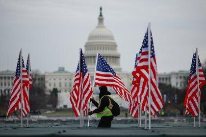 Un trabajador instala una bandera de los Estados Unidos para exhibirla en el National Mall, como parte del homenaje que prepare Biden para las víctimas de coronavirus en el país. REUTERS / Carlos Barria