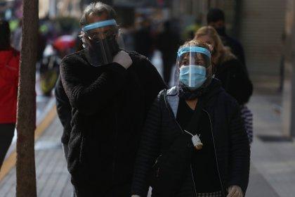 Dos ciudadanos protegidos con mascarilla y careta caminan por el principal corredor peatonal del centro en Santiago (Chile). EFE/ Elvis González/Archivo
