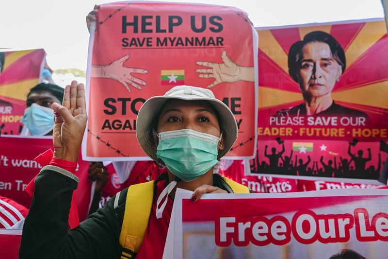 A demonstrator flashes a three-finger salute while holding a sign to protest against the military coup and demand for the release of elected leader Aung San Suu Kyi, in Yangon, Myanmar, February 12, 2021. REUTERS/Stringer