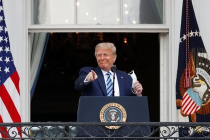 "U.S. President Donald Trump gestures as he stands on a White House balcony speaking to supporters gathered on the South Lawn for a campaign rally that the White House is calling a ""peaceful protest"" in Washington, U.S., October 10, 2020. REUTERS/Tom Brenner"