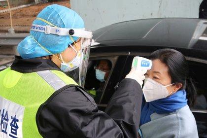 Un oficial de seguridad con una máscara protectora verifica la temperatura de un pasajero tras el brote de un nuevo coronavirus en un peaje en vísperas de las celebraciones por el Año Nuevo Lunar chino, en Xianning, provincia de Hubei. 24 de enero de 2020. REUTERS/Martin Pollard