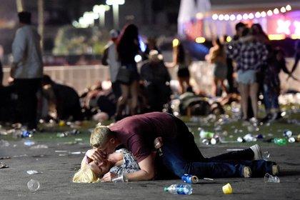 Matthew Cobos intenta consolar a una mujer herida durante el concierto en Las Vegas, que terminó en una masacre (Getty Images)