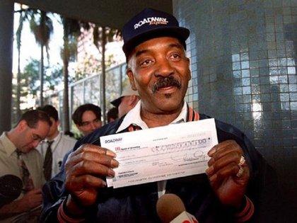 Willie Fullgear mostrando a las cámaras de TV el cheque de USD 50.000 que recibió de recompensa