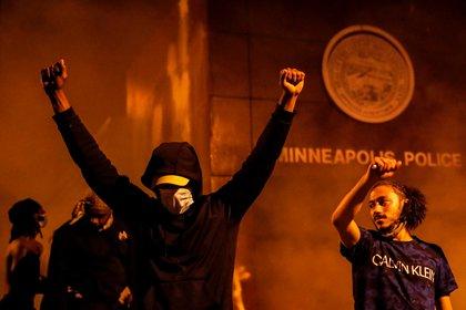 Un manifestante celebra ante la estación de policía en llamas (Reuters/ Carlos Barria)