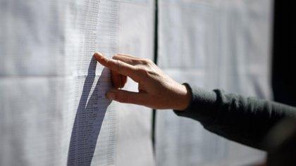 AME6109. BUENOS AIRES (ARGENTINA), 11/08/2019.- Personas buscan información sobre su punto de votación este domingo en Buenos Aires (Argentina). Unos 33,8 millones de argentinos deben acudir hoy a las urnas para optar entre las diez fórmulas presidenciales que en estas primarias buscan quedar habilitadas para la competencia de octubre. EFE/Juan Ignacio Roncoroni