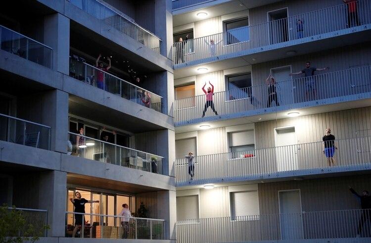 Como los gimnasios están cerrados, muchas personas hacen ejercicio en los balcones (REUTERS/Stephane Mahe)