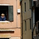 FILE PHOTO: A woman looks out of an apartment window as Italians remain under lockdown to prevent the spread of the coronavirus disease (COVID-19) in Venice, Italy April 4, 2020. REUTERS/Manuel Silvestri/File Photo