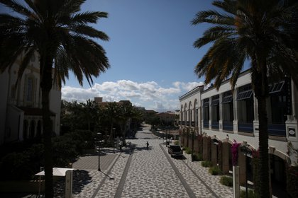 Un hombre camina a lo largo de una área comercial vacía el 24 de marzo de 2020 después de que las autoridades locales restringieran las actividades de restaurantes, bares, gimnasios, cines y otros negocios similares por precaución debido a la enfermedad coronavirus (COVID-19) propagada en West Palm Beach, Florida (REUTERS/Carlos Barria)