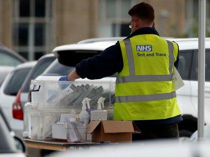 Un trabajador sanitario británico manipula pruebas de coronavirus en un centro de testeo. Foto: REUTERS/Phil Noble