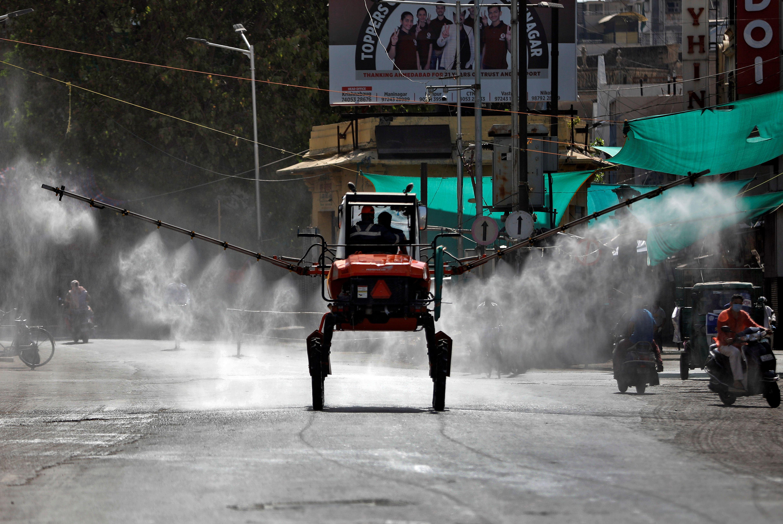 Miembros de los Servicios de Bomberos y Emergencias descontaminan una carretera utilizando un pulverizador de barra en Ahmedabad, India, el 24 de abril de 2020. REUTERS/Amit Dave