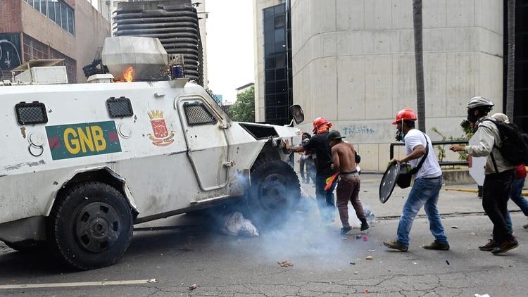 Una tanqueta de la GNB arrolla a manifestantes opositores (AFP)
