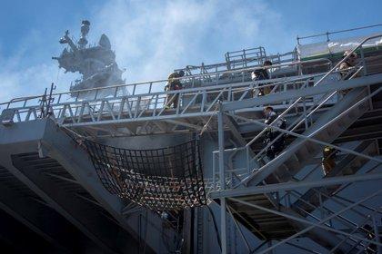 Cette photo du 14 juillet 2020 fournie par la marine américaine montre des marins et des pompiers du service fédéral des incendies de San Diego alors qu'ils combattent un incendie à bord du navire d'assaut amphibie USS Bonhomme Richard (DG 6), à la base navale de San Diego, Californie (États-Unis) ).  EFE / Jessica Paulauskas / US Navy