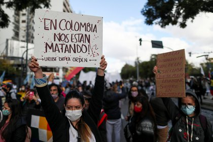 """A demonstrator holds a placard that reads """"In Colombia they are killing us"""", during a protest against what they say was police brutality exerted in recent protests in Colombia against President Ivan Duque's government's tax reform, outside the Colombian consulate in Buenos Aires, Argentina May 4, 2021. REUTERS/Agustin Marcarian"""