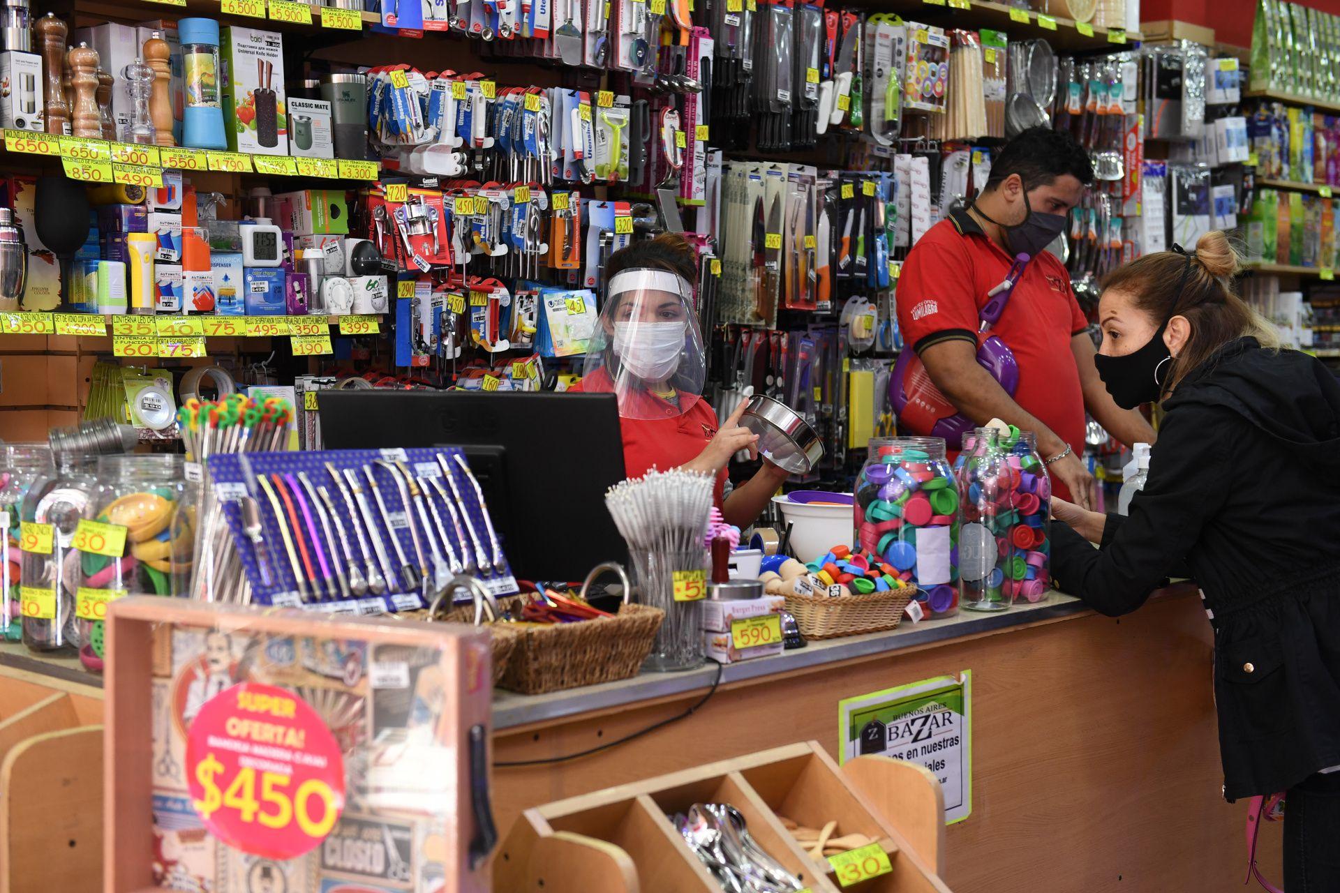 Una cajera con barbijo y máscara de protección le cobra a una clienta en un bazar del barrio porteño de Belgrano