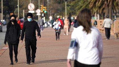 Gente con barbijo camina por Montevideo (Reuters)