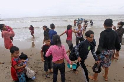 Los menores venezolanos descienden del bote en la playa Los Iros, en Erin (Lincoln Holder/Cortesía Newsday/Handout vía REUTERS)