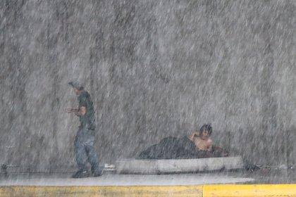 Dos vecinos de la calle se protegen de la lluvia en una céntrica avenida de Monterrey (México).  EFE / Mar & # 237;  una Julia Casta & # 241;  eda