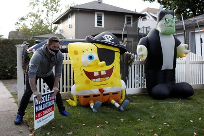 Bobby Grant, a campaign volunteer for Republican congressional candidate for New York's 11th district Nicole Malliotakis, places a lawn sign in front of Halloween decorations on Staten Island in New York City, U.S., October 3, 2020. Picture taken October 3, 2020. REUTERS/Andrew Kelly