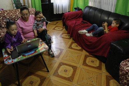 Denisse sostiene a su hijo Fer de un año, ayuda a su hija Liz, de 5 años, con una clase de prejardín de infantes en línea, mientras su hijo Santi, de 6, se sienta en el sofá después de ver una lección de jardín de infantes televisada en su hogar. (Foto AP / Rebecca Blackwell)