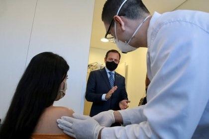 Un voluntario recibe la primera prueba de la posible vacuna contra el coronavirus Sinovac de China en presencia del gobernador Joao Doria