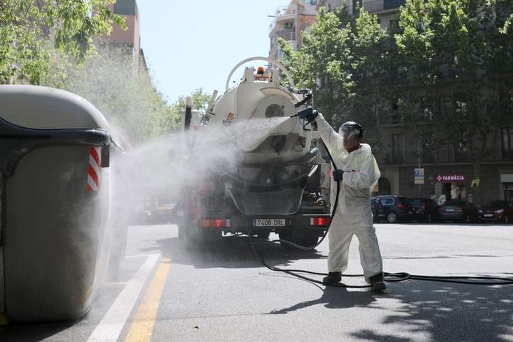 Un trabajador desinfecta unos contenedores de basura, después del brote de la enfermedad coronavirus (COVID-19) en Barcelona, España, el 14 de abril de 2020. (REUTERS/Nacho Doce)