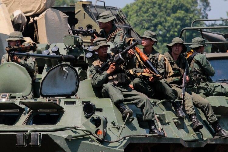 Un grupo de soldados venezolanos sentados sobre un vehículo BTR-80A. Están armados con lanzagranadas, lanzamisiles RPG-7V, Carl Gustav M2 y fusiles Ak-103 (AFP)