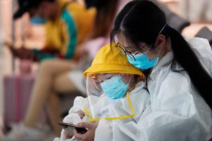 Una mujer y su hijo en el aeropuerto de Wuhan.  REUTERS/Aly Song
