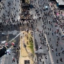 Aerial view of a police water cannon spraying at demonstrators in Santiago on November 12, 2019. - Chile has announced it will move to draft a new constitution and replace one dating back to the Augusto Pinochet dictatorship -- a key demand of protesters who have rocked the country for over three weeks. (Photo by JAVIER TORRES / AFP)
