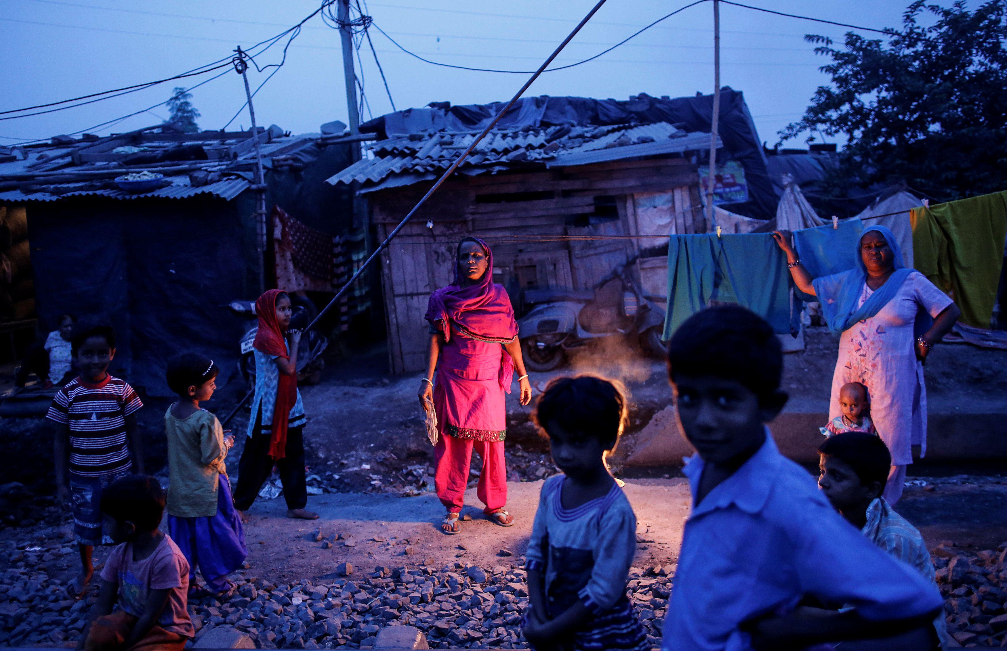 Subna Bi (centro de la imagen), de 55 años, posa para una foto en el exterior de su casa, junto a la antigua planta abandonada de pesticidas Union Carbide Corp, en Bhopal, el 15 de noviembre de 2014.
