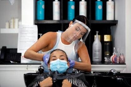 Una peluquera con protector facial lava el pelo de una cliente en Newport Pagnell, Gran Bretaña,