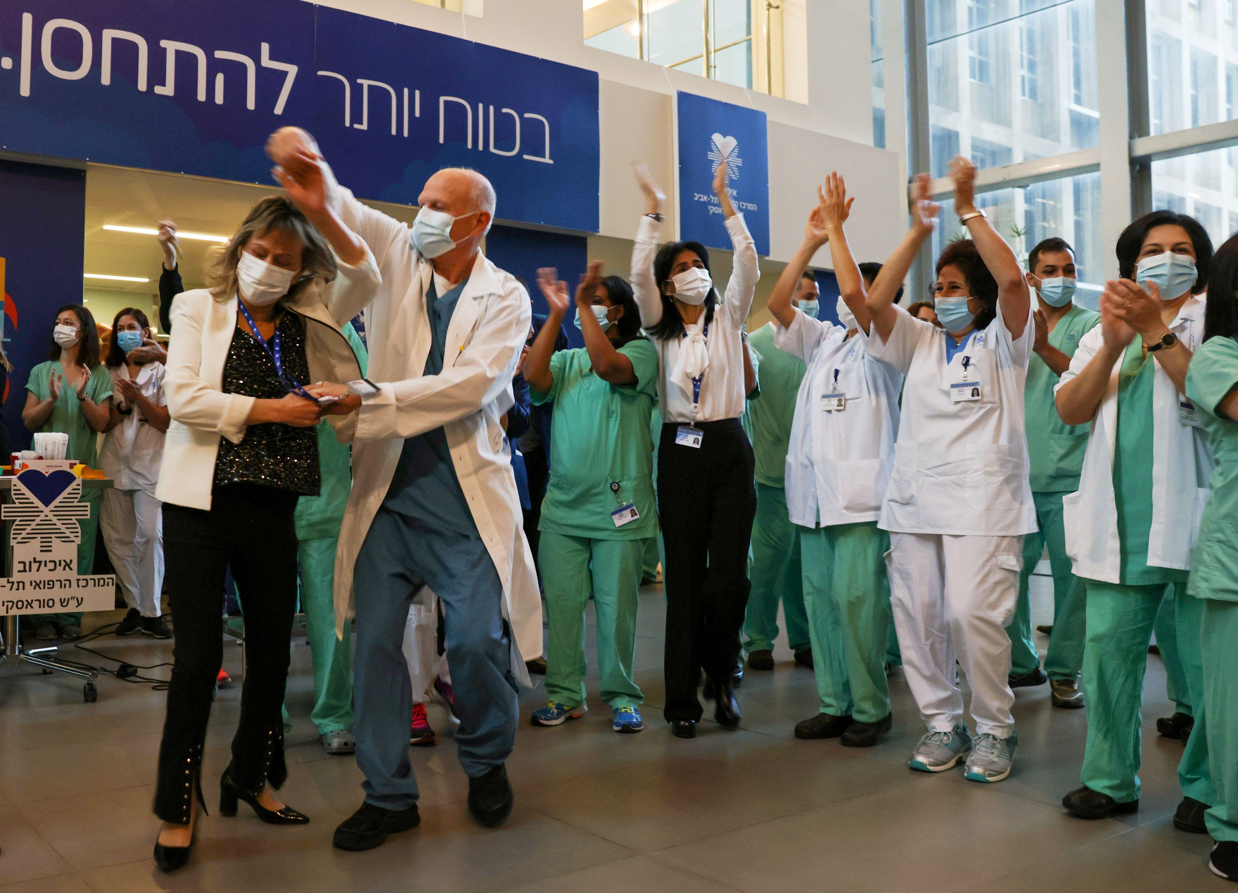 Profesionales de la salud celebran luego de recibir la vacuna contra el COVID-19 en un hospital de Tel Aviv, Israel (REUTERS/Ronen Zvulun)