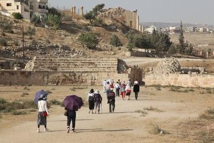 Une photo prise le 6 novembre 2019 montre des touristes marchant dans l'ancienne ville romaine jordanienne de Jerash, une attraction populaire à 50 km au nord de la capitale Amman.  (Photo par Ahmad ABDO / AFP)