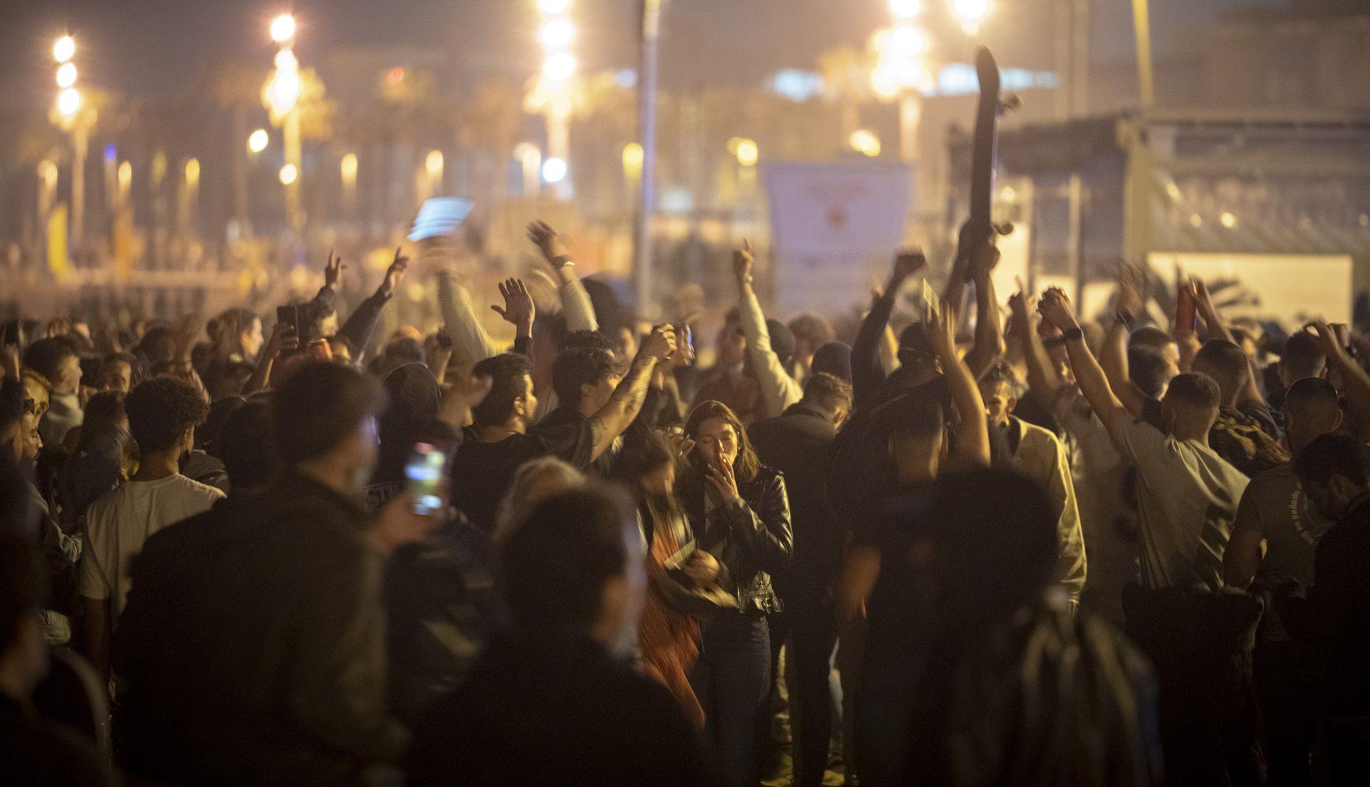 Gente bailando en una multitud en la playa de Barcelona, España, el domingo 9 de mayo de 2021. Celebraciones improvisadas tomaron las calles en distintos lugares de España cuando llegó la medianoche del sábado y expiró el estado de alarma de seis meses para contener los contagios de coronavirus, lo que levantó los toques de queda en muchas regiones. (AP foto/Emilio Morenatti)