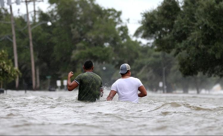 Residentes caminan por las calles inundades de Mandeville (Reuters)