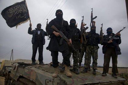 Combatientes de Hayat Tahrir Al Sham sobre un tanque capturado