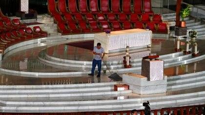 Un trabajador limpia el piso antes que el cardenal de la iglesia Católica mexicana, Carlos Aguiar, celebre una misa a través de YouTube, en Ciudad de México, México. 22 de marzo de 2020. REUTERS/Henry Romero