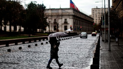 01/07/2020 01 July 2020, Chile, Santiago: A woman holds an umbrella as she walks through an almost empty street following the Chilean government decision to extend the strict exit restrictions to contain the spread of the coronavirus pandemic. Photo: Cristobal Escobar/Agencia Uno/dpa POLITICA INTERNACIONAL Cristobal Escobar/Agencia Uno/dp / DPA