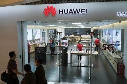 Varias personas con mascarillas caminan frente a una tienda de Huawei en un centro comercial de Pekín, China, el 18 de mayo de 2020. REUTERS/Carlos García Rawlins