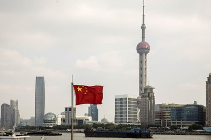 A Chinese national flag flies as skyscrapers of the Pudong Lujiazui Financial District stand across the Huangpu River in Shanghai, China, on Friday, Dec. 28, 2018. China announced plans to rein in the expansion of lending by the nation's regional banks to areas beyond their home bases, the latest step policy makers have taken to defend against financial risk in the world's second-biggest economy. Photographer: Qilai Shen/Bloomberg