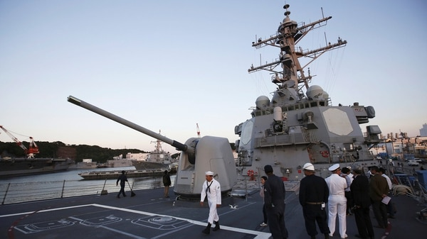 Marineros observan el barco en la cubierta del Milius (Reuters)