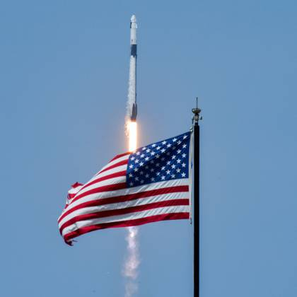 An American flag is seen as SpaceX Falcon 9 rocket and Crew Dragon spacecraft carrying NASA astronauts Douglas Hurley and Robert Behnken lifts off during NASA's SpaceX Demo-2 mission to the International Space Station from NASA's Kennedy Space Center in Cape Canaveral, Florida, U.S. May 30, 2020. REUTERS/Steve Nesius     TPX IMAGES OF THE DAY